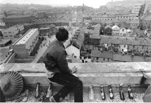 A youth armed with molotov cocktails keeps guard on top of a highrise flat in Derry.